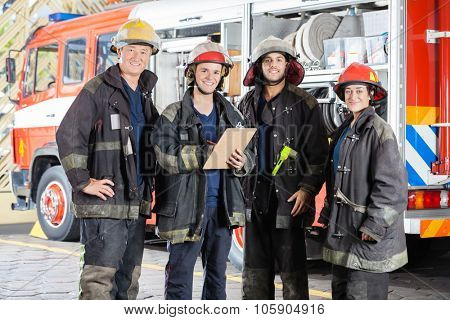 Portrait of happy firefighters standing together at fire station
