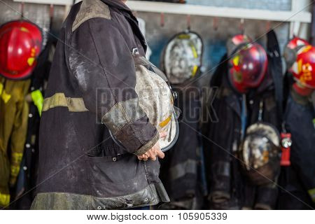 Midsection side view of fireman holding helmet at fire station