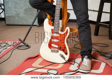 Low section of male performer with guitar in recording studio