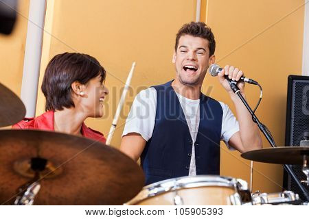 Happy male singer performing while looking at female drummer in studio