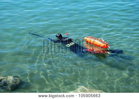 Man with harpoon in shallow water.