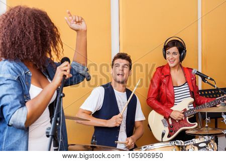 Happy drummer and guitarist looking at woman singing in recording studio