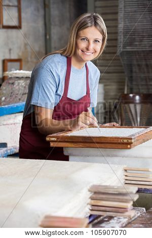 Portrait of smiling female worker cleaning paper with tweezers in factory