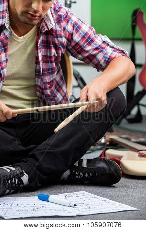 Low section of young man practicing with drumsticks while sitting on floor in recording studio