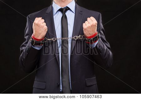 man in a business suit with chained hands. handcuffs for sex games