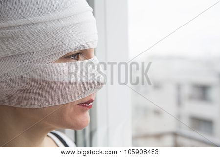 Woman In Bandages Looking Out Of A Window