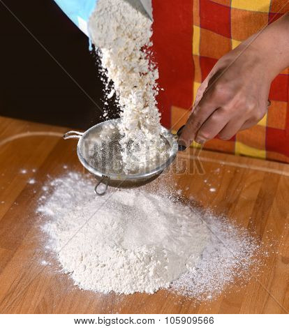 Woman Sifting Flour Through A Sieve