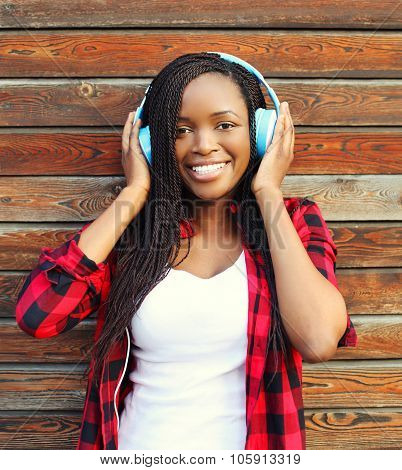 Beautiful Smiling African Woman With Headphones Listens To Music And Having Fun In City Over Wooden