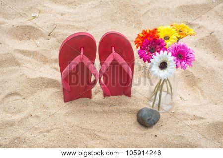 Red Old Slippers And Flower On The Sand