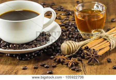 Coffee On The Cup With Coffee Beans, Honey And Cinnamon Sticks On Wood Background, Warm Toning, Sele