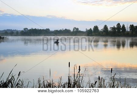 A Fisherman In A Boat Sailing In The Morning Mist