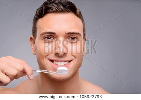 Handsome man cleaning teeth
