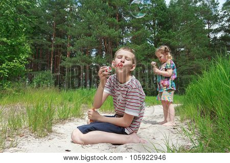 Two Sibling Children Playing With Soap Bubbles On Sand Dune Beach At Pinewood Background