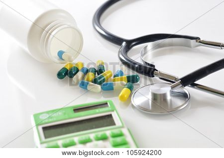 Capsule Pills Spill out From Bottle with Stethoscope and Calculator on White Background