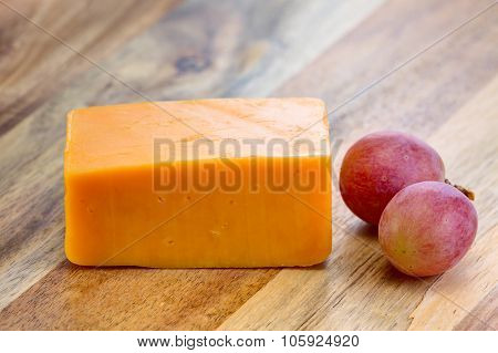 Red cheddar cheese with grapes on the wooden board