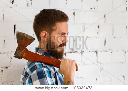 Young bearded lumberjack with red axe
