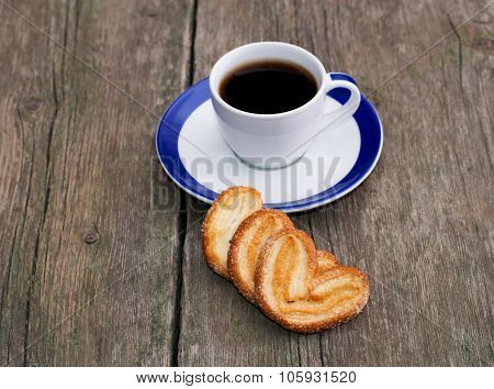 Cup Of Coffee And Three Cookies In A Row In Front, On A Wooden Table