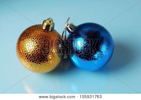 Golden and blue christmass balls on a glass background