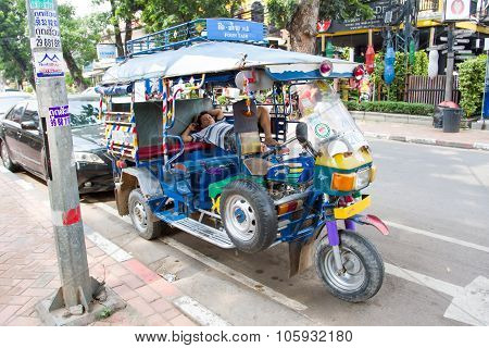 A tuk tuks or songthaews parked on the side of the main road