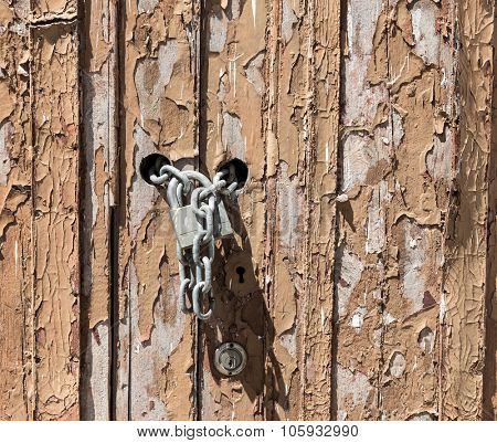 Old wooden ragged door locked close up
