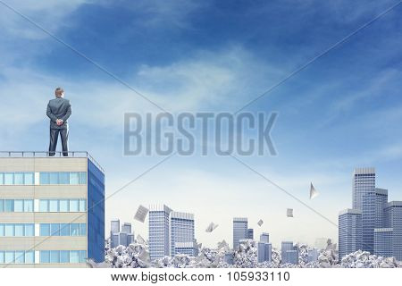 Businessman is looking at the horizon over the city sinking in paperwork