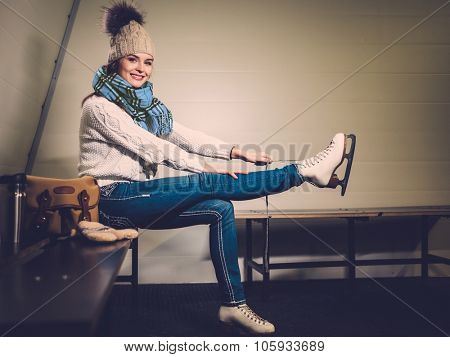 Cheerful girl putting on skates  in locker room