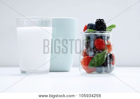 Jar With Berries And Mint Located On White Table With Glass Of Milk And Blue Glass In Line
