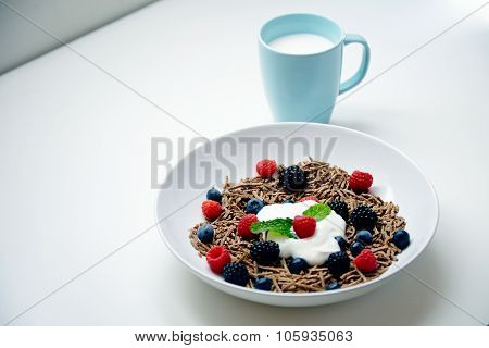 Glass Of Milk And Plate With Berries And Integral Musli Dipped With Yougur