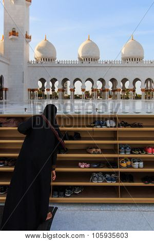 Abu Dhabi, United Arab Emirates - October 10,2014: Woman Taking Off Her Shoes Before Entering The Sh