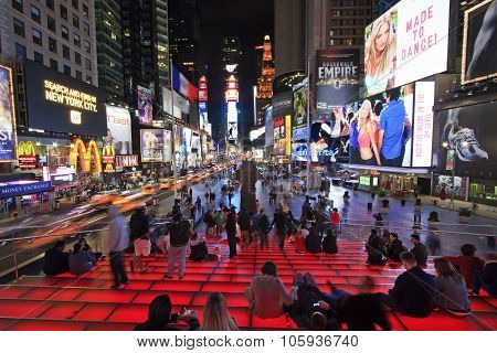 New York, United States - June 5 2012: Times Square by night with many tourists enjoying the scene