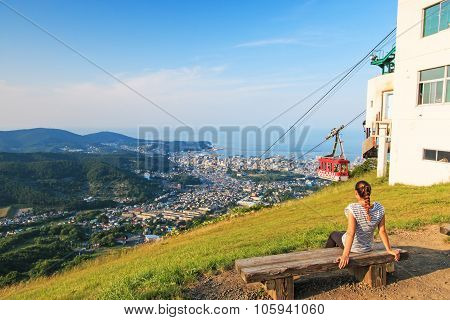 Otaru, Japan - July 11,2015: Girl Watching The Cityscape Of Otaru In Hokkaido With A Cableway On Her