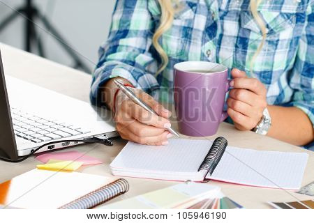 Female designer hands holding cup of hot beverage and drawing with pen