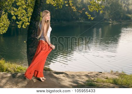 Beautiful Young Blonde Woman Posing Under The Tree On Riverbank