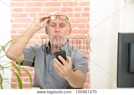 Mature man having trouble seeing phone screen because of vision problems