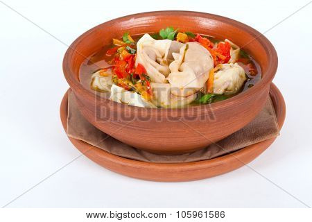 soup with dumplings and vegetables clay brown pot isolated white background