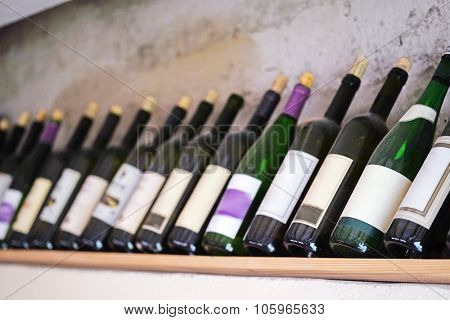 The image of  bottles of  wine on a wooden shelf in the restaurant