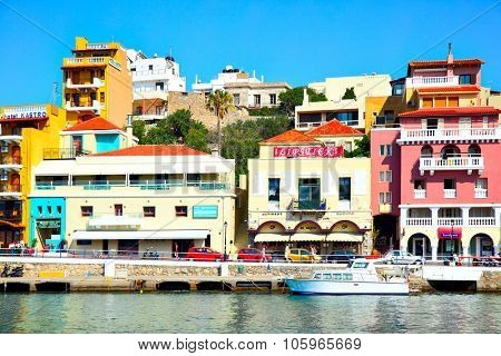 AGIOS NIKOLAOS, GREECE - JUNE 30, 2015: Picturesque waterfront with hotels, taverns, shops and boats in harbor in Agios Nikolaos, Crete Island