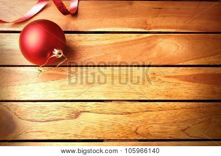 Red Ball And Ribbon Christmas Decoration On Wooden Table Top