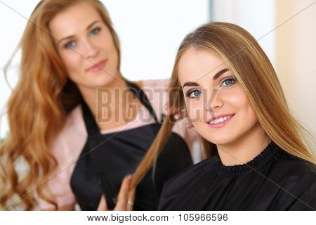 Beautiful Blonde Female Hairdresser Holding Lock Of Hair
