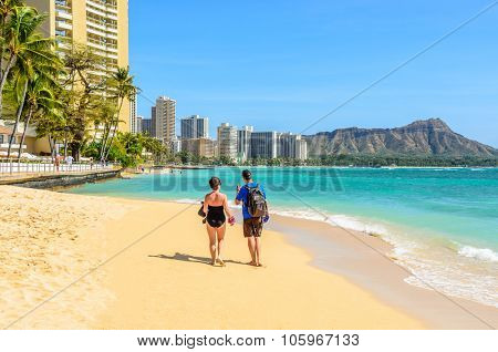 Couple walking on beach. Young happy interracial couple walking on beach talking holding around each other.