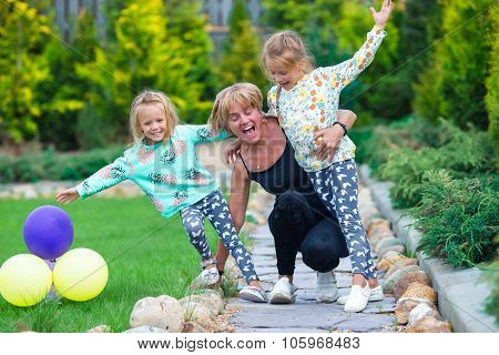 Little adorable girls having fun with happy grandmother in summer day outdoors