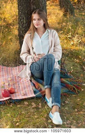 Young Woman Resting In A Park In Autumn.