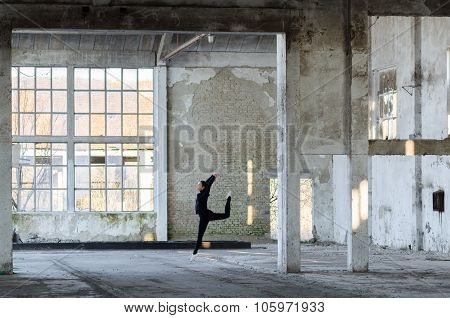 Young Modern Ballerina Exercising And Dancing In Abandoned Building