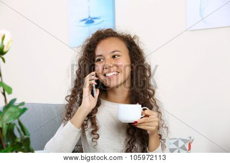 Close up portrait of young woman speaking by cellphone with cup of coffee in the room
