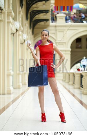 Beautiful smiling girl in a red dress, holding shopping bags walking in the shop