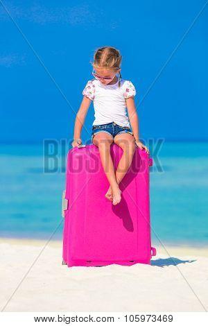 Little adorable girl with big luggage on tropical island