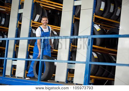 smiling auto mechanic has sold a car tire in tire store