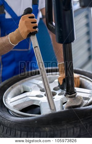 repairman with installer replace tire on wheel  in workshop