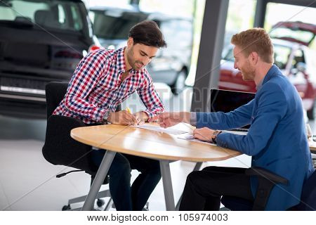 man buying a car and car signs the contract in car showroom