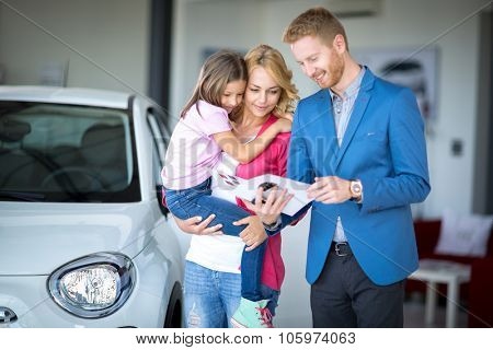 car dealer showing brochure young woman with child at car dealership saloon